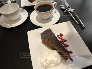 コーヒー カップの横にある皿の上のケーキの一部の写真・画像素材[805895]