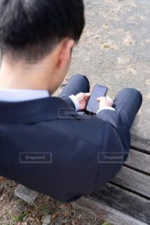 ベンチに座ってスマートフォンをいじっている男性の写真・画像素材[4221407]