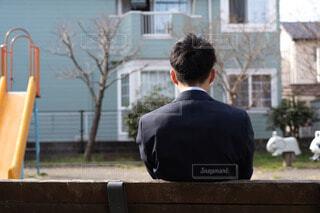 公園のベンチに座っている男性の後ろ姿の写真・画像素材[4221403]
