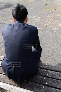 公園のベンチに座って考え事をしている男性の写真・画像素材[4221404]