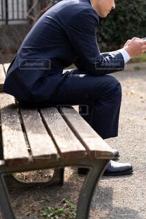 公園のベンチに座ってスマートフォンをいじっている男性の写真・画像素材[4221408]