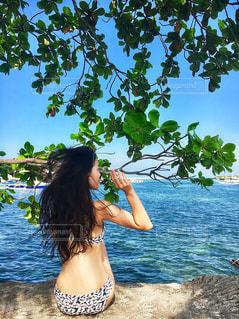 水の体の横に立っている人の写真・画像素材[1117881]