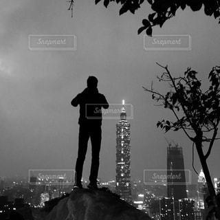 像山頂上の岩の上から夜景と台北101を撮影している観光客の写真・画像素材[953044]