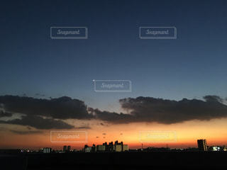 バック グラウンドで市と水体に沈む夕日の写真・画像素材[927671]