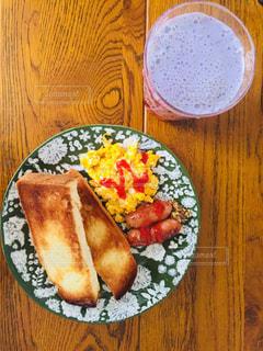木製のテーブルの上に食べ物のプレートの写真・画像素材[1037038]