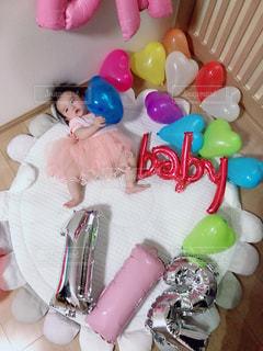 バースデーケーキを持ってテーブルに座っている小さな女の子の写真・画像素材[2342817]