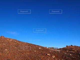 岩が多い丘の上に立っている人の写真・画像素材[800511]