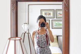 カメラにポーズ鏡の前に立っている人の写真・画像素材[1831021]