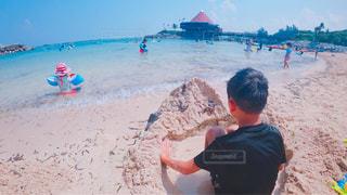 ビーチの砂の上に立っている小さな男の子の写真・画像素材[1385783]