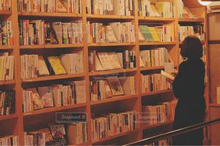 本棚の前に立っている人の写真・画像素材[2893066]