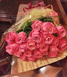 テーブルの上のピンクの花でいっぱいのボックスの写真・画像素材[1374368]