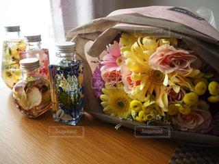 テーブルの上に座っての花で一杯の花瓶の写真・画像素材[1374373]