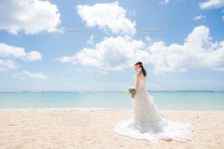 水の体の近くのビーチに立っている男の写真・画像素材[3265558]
