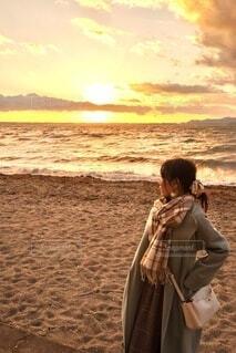 女性,20代,自然,海,冬,朝日,砂,ビーチ,砂浜,コート,マフラー,夕暮れ,水面,海岸,人,立つ,正月,お正月,黄昏,夕陽,日の出,サンセット,新年,初日の出,眺める