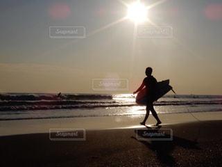 ビーチの上を歩くサーフボードを運ぶ男の写真・画像素材[967725]