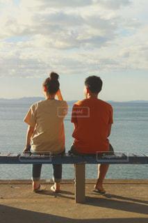 男と女は水の体の横にあるベンチに座っての写真・画像素材[1629714]