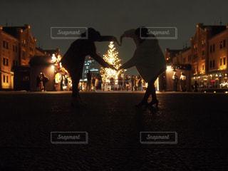暗闇の中に立っている人々 のグループの写真・画像素材[918605]