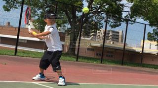 裁判所にラケットでボールを打つ男の写真・画像素材[1321763]