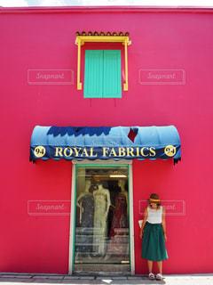 赤いドアの前に立っている女性の写真・画像素材[843437]