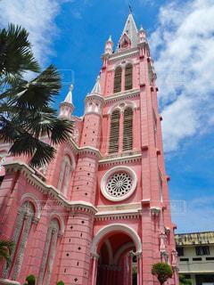 建物の側に時計と大きな背の高い塔の写真・画像素材[916660]