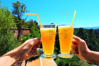 オレンジ ジュースのガラスを保持している人 - No.927407