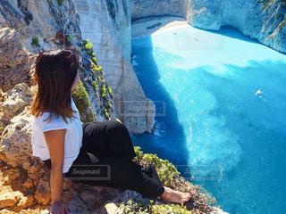 岩の上に座っている女性の写真・画像素材[955628]