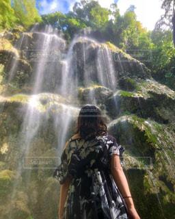 滝の隣に立っている人の写真・画像素材[1451521]