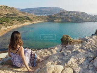 水の体の横にある岩に座っている女の子の写真・画像素材[1685516]