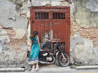 レンガ造りの建物の前に立っている人の写真・画像素材[2234339]