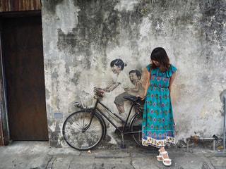 自転車の前に立っている女性の写真・画像素材[2234341]
