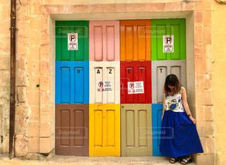 青いドアの前に立っている人の写真・画像素材[2234409]