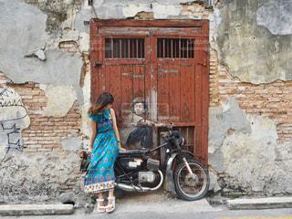 レンガ造りの建物の前に立っている人の写真・画像素材[3190284]