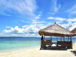 砂浜の上に座っている青い傘の写真・画像素材[3339946]