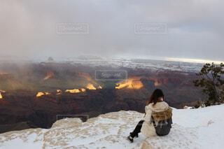 雪に覆われた山の上に座っている人の写真・画像素材[3840865]