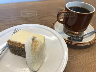 コーヒー カップの横にある皿の上のケーキの一部の写真・画像素材[815915]