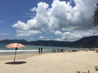 曇りの日にビーチ パラソルに座っている人々 のグループの写真・画像素材[1317744]