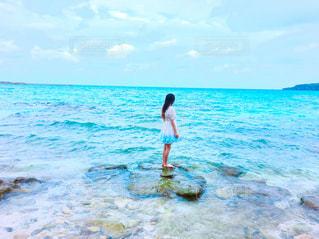 水の体の横に立っている人の写真・画像素材[908484]