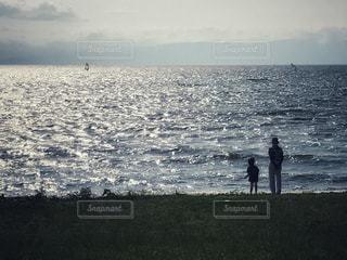 水域の隣に立っている男の写真・画像素材[2328464]