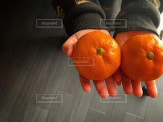 食べ物,屋内,手,子供,オレンジ,手持ち,果物,床,人物,みかん,こども,ポートレート,ライフスタイル,手元,子供の手,ミカン,2つ,二個