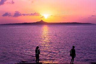 水の体の上に夕日の前に立っている男の写真・画像素材[2264023]