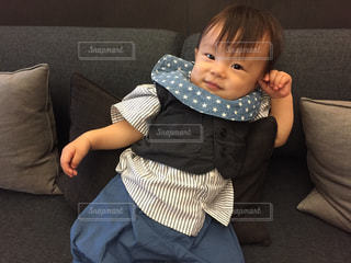 小さな子供、赤ちゃんを保持しているソファに座って - No.887051