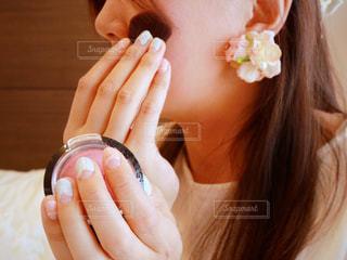彼女の顔に彼女の手を保持している女性の写真・画像素材[1175584]