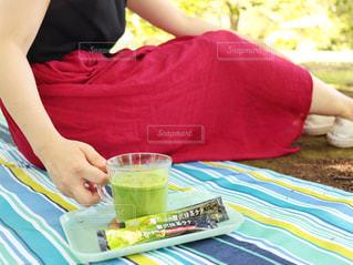 ピクニック用のテーブルに座っている女性の写真・画像素材[1277238]