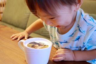 一杯のコーヒーをテーブルに座って男の子の写真・画像素材[1456446]