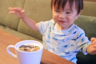 一杯のコーヒーをテーブルに座って男の子の写真・画像素材[1456467]