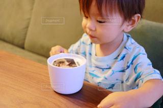 一杯のコーヒーをテーブルに座って男の子の写真・画像素材[1456479]