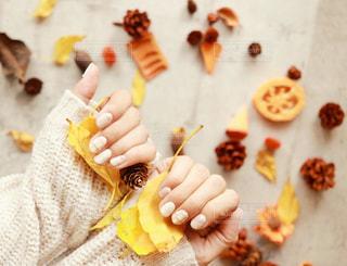 秋ネイルと枯葉の写真・画像素材[1523086]