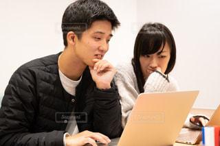 男とラップトップを使用してテーブルに座っている女性の写真・画像素材[1651707]