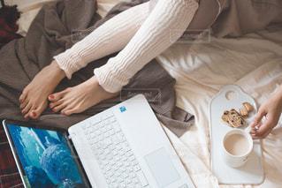 ベッドの上でノート パソコンをテーブルに着席した人の写真・画像素材[1660353]