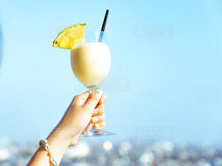 オレンジ ジュースのグラスを持っている手の写真・画像素材[1822938]